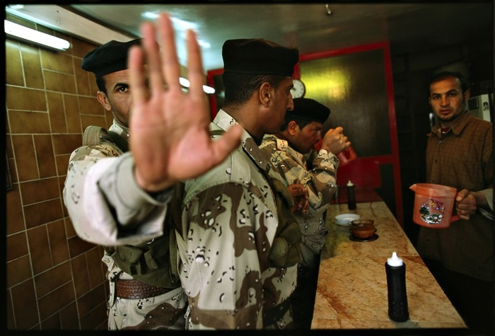 "Alexandra Boulat/VII, ""Baghdad before the bombs. 'Enough pictures!' said this soldier, stopping for tea at one of the city's many falafel stands"", March 5, 2003, digital C-print, 20x24""."