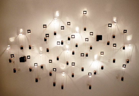 """Michael Rauner, """"Reliquary DNA"""", 1999, mixed media instillation with light bulbs, color slides, copper wire, and batteries."""