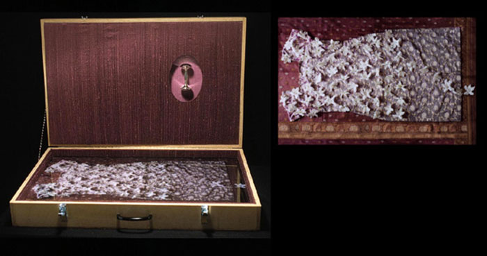 "Priya Kambli, ""Purple"", from ""Suitcase"" series, 2003, mixed media (photograph, baby rattle, & purple silk), 19x29x5½"""