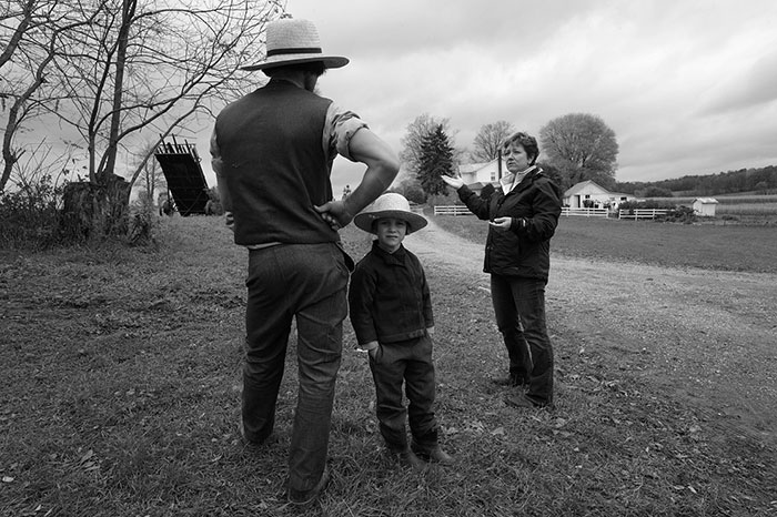"Lynn Johnson, ""Carrie Hahn, an activist, talks to an Amish farmer about the hazards of allowing a gas-drilling operation on his land in New Wilmington, PA"", archival pigment print, 16x21""."